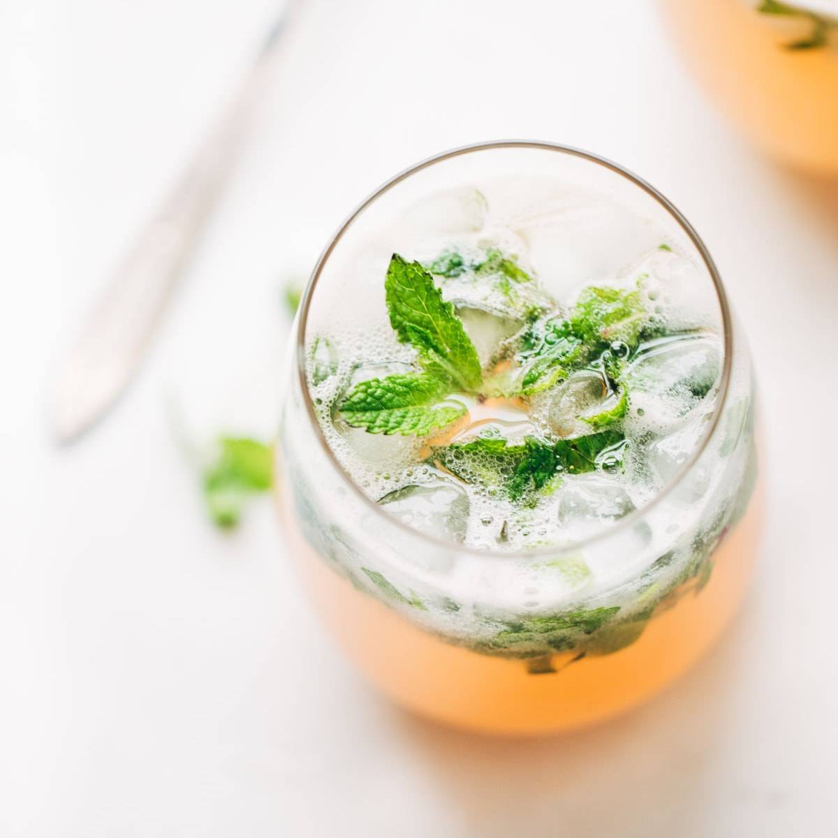 Grapefruit Mojitos in a glass with mint leaves.