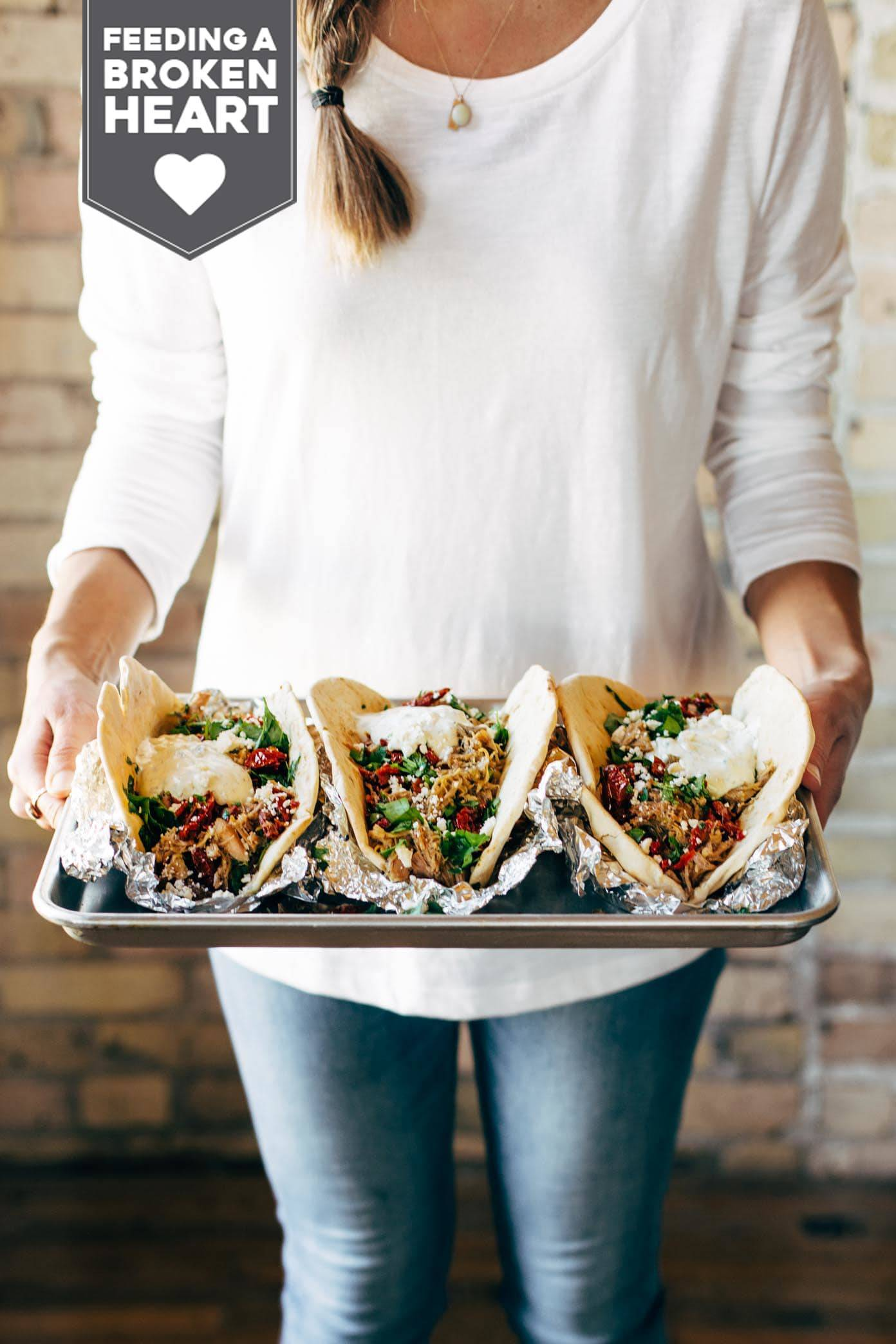 Woman holding a tray of Everything Greek Pork Pitas