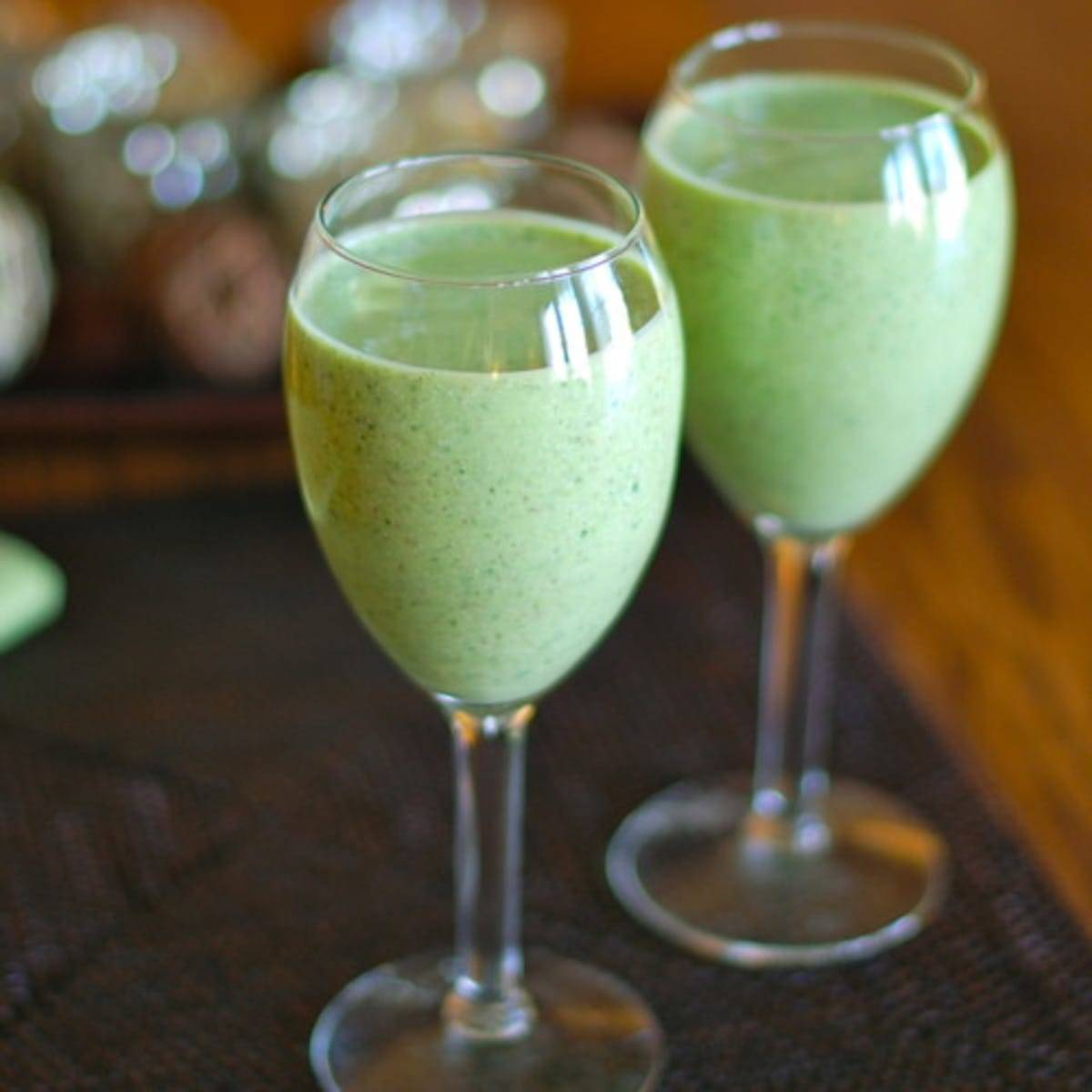 Two green monster smoothies in glasses.