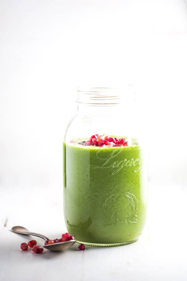 Green apple smoothie with pomegranate seeds.