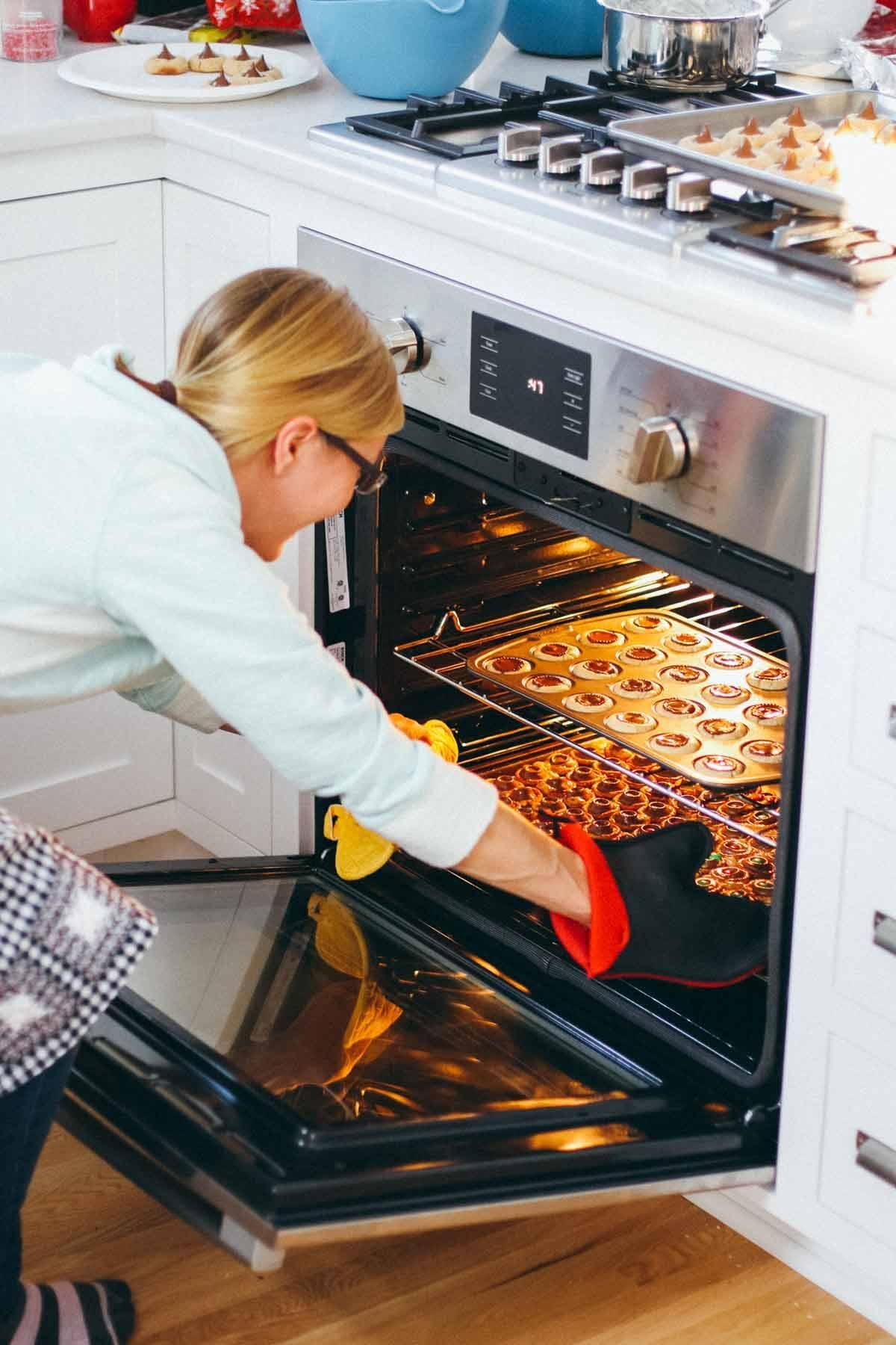 Woman pulling cookies out of an oven.
