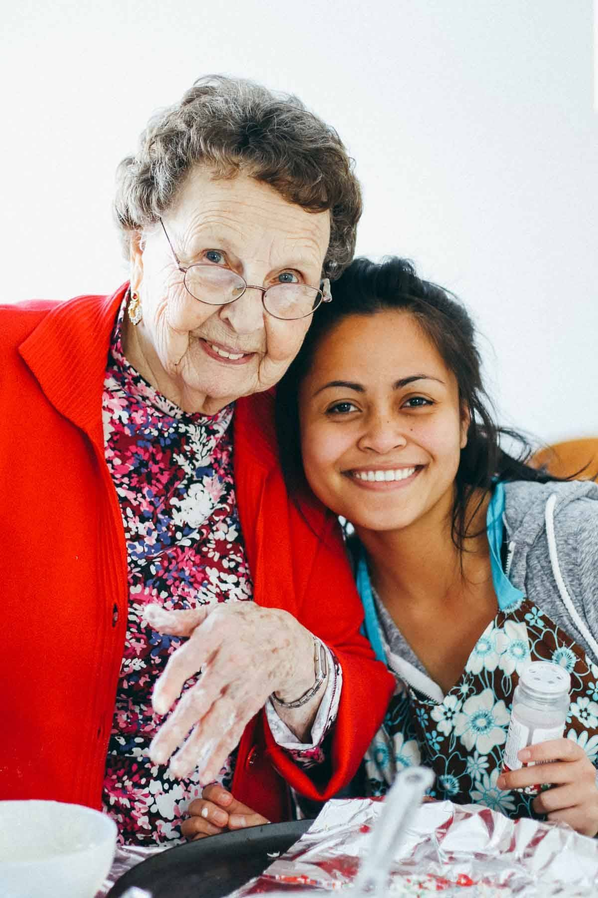 Elderly woman smiling with a young girl.
