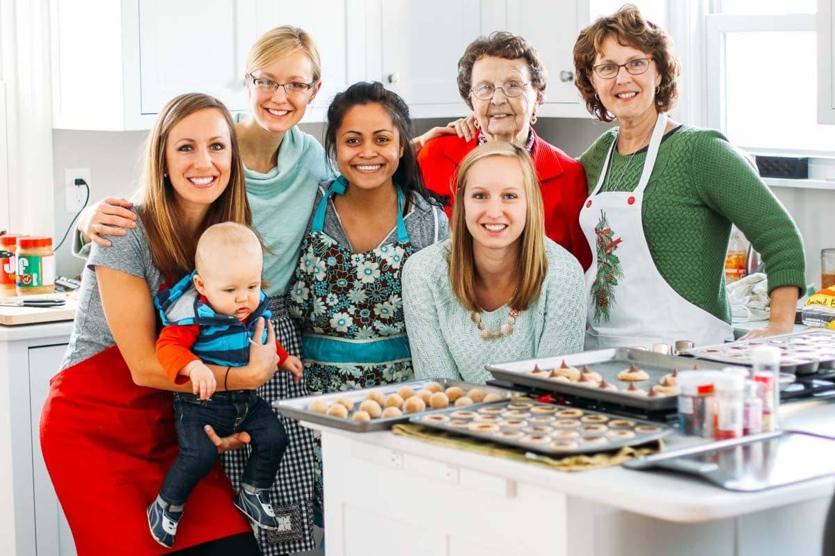 Women and a baby boy in a kitchen.