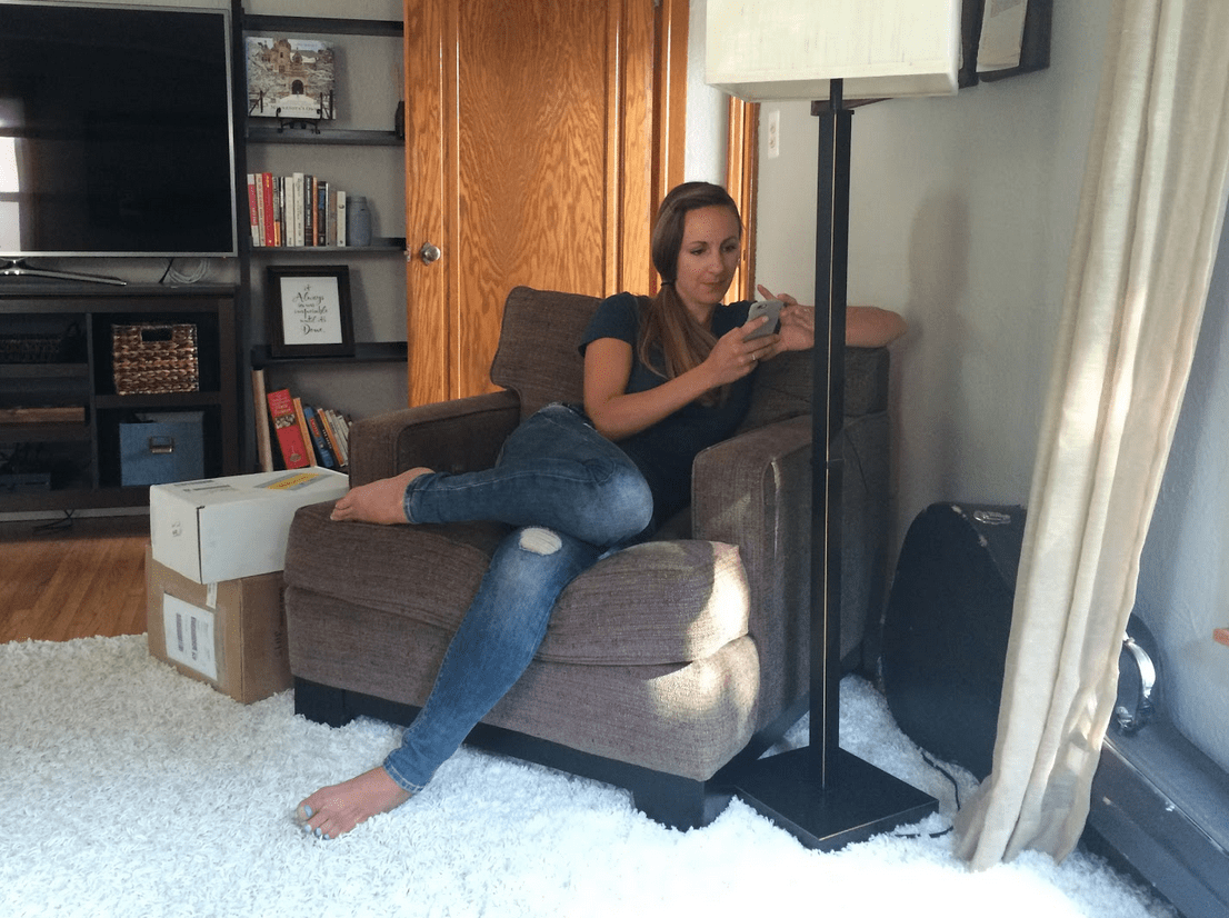Woman sitting on her phone in a chair.