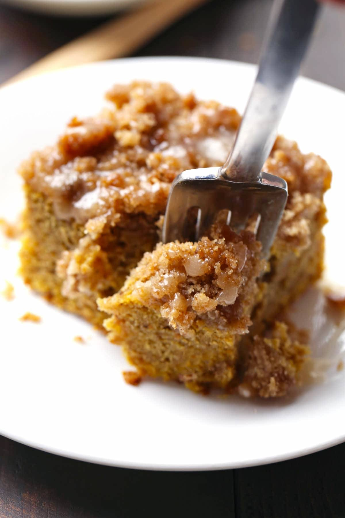 Cinnamon Streusel Pumpkin Coffee Cake with Maple Glaze on a white plate with a fork.