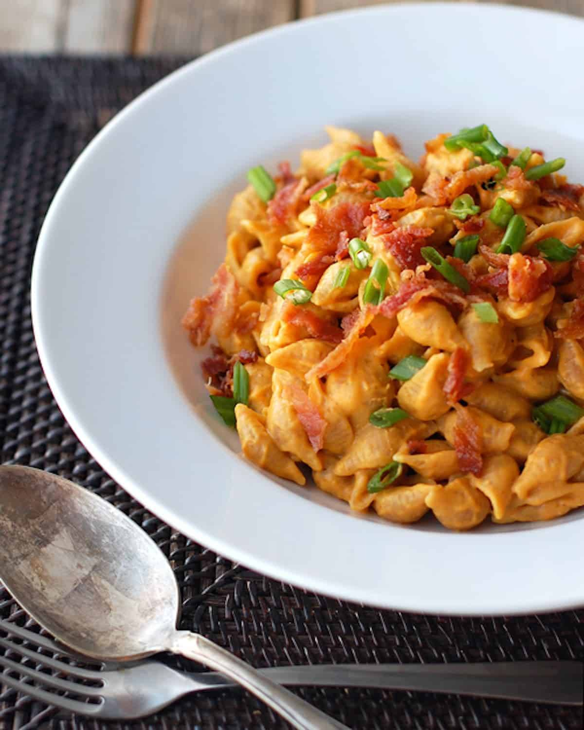 Bacon and pumpkin pasta with creamy pumpkin sauce, whole wheat pasta shells, and crumbled bacon in a white bowl with a spoon and a fork.