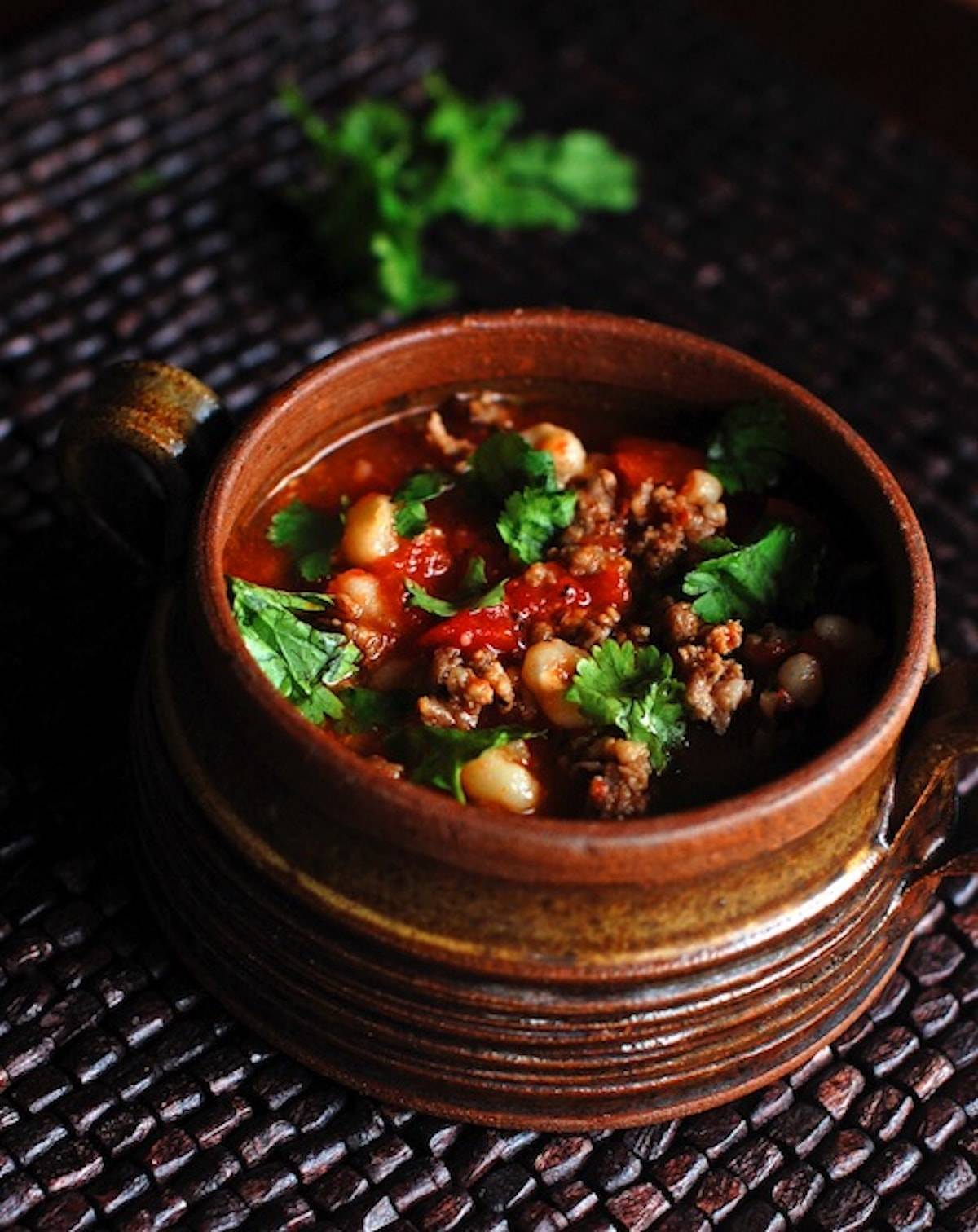 Spicy sausage posole in a unique bowl with herb topping.