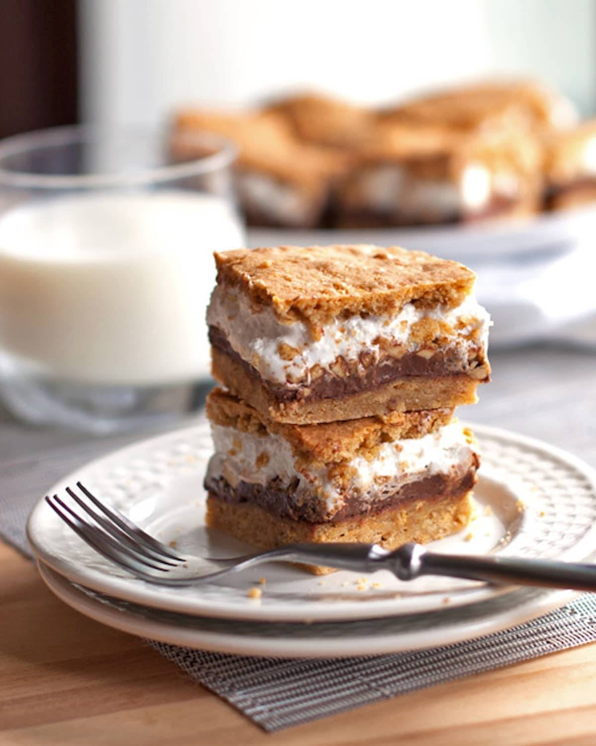 These s'mores bars have peanut butter layered in between marshmallow fluff, chocolate, and a graham cookie base. Just like s'mores! | pinchofyum.com