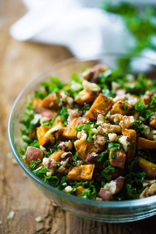 This Roasted Sweet Potato Salad has a handful of shredded kale, candied walnuts, and the best creamy almond dressing. Yum! | pinchofyum.com