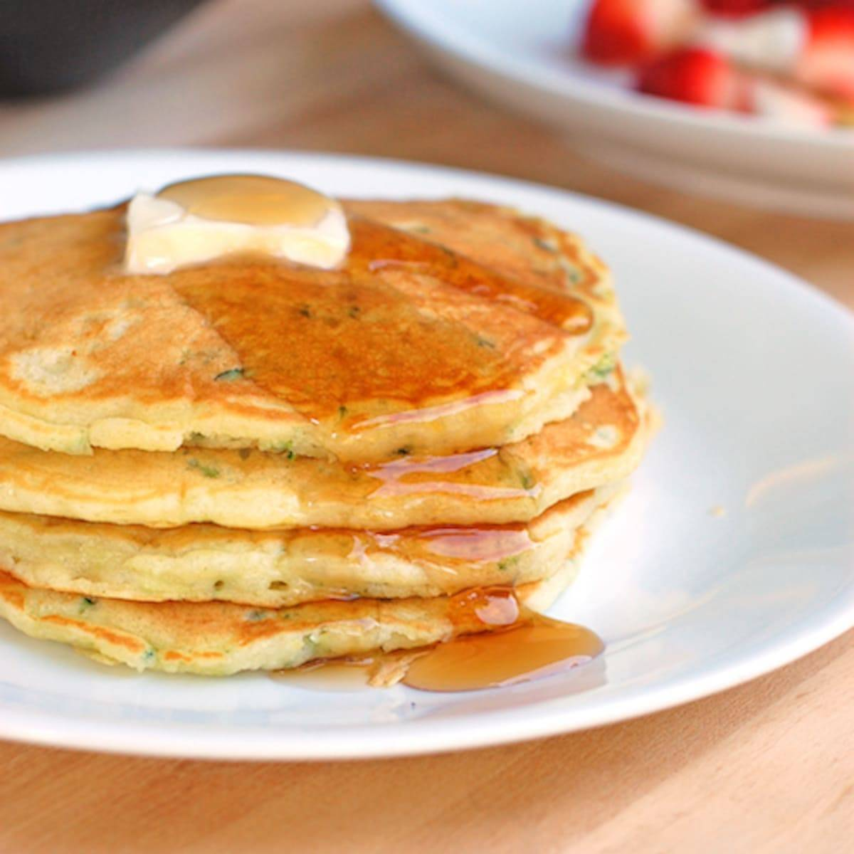Stack of zucchini pancakes with butter and maple syrup.