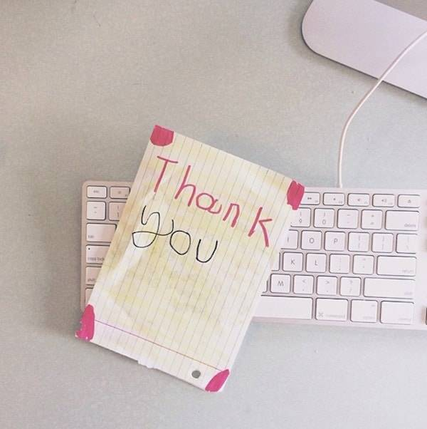 Thank you note laying on a keyboard.