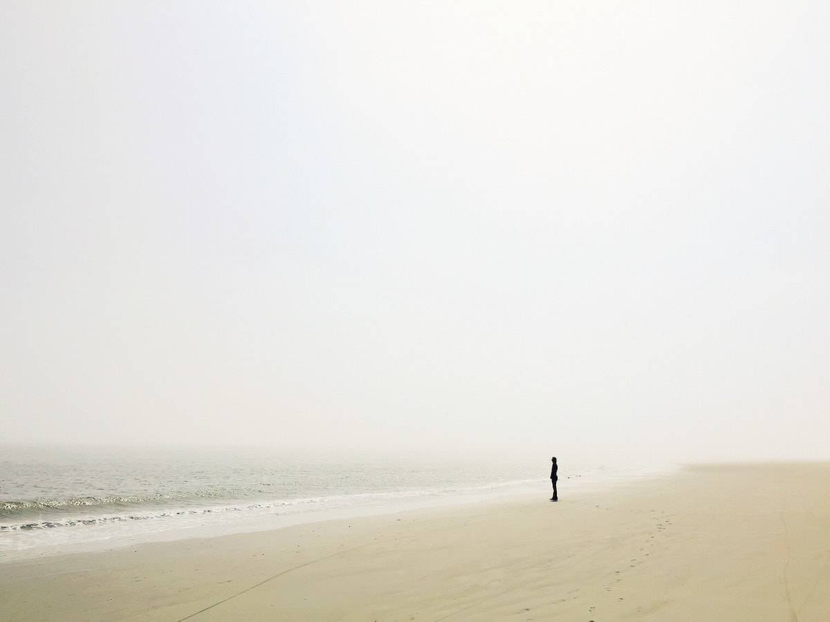 Tiny person standing on the ocean shore.