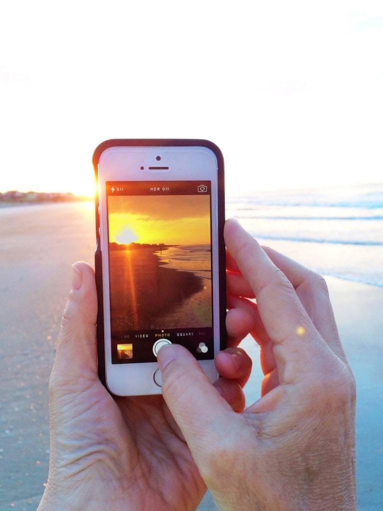 Iphone taking a photo of a sunrise.