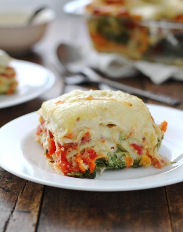 Veggie Alfredo lasagna on a white plate.