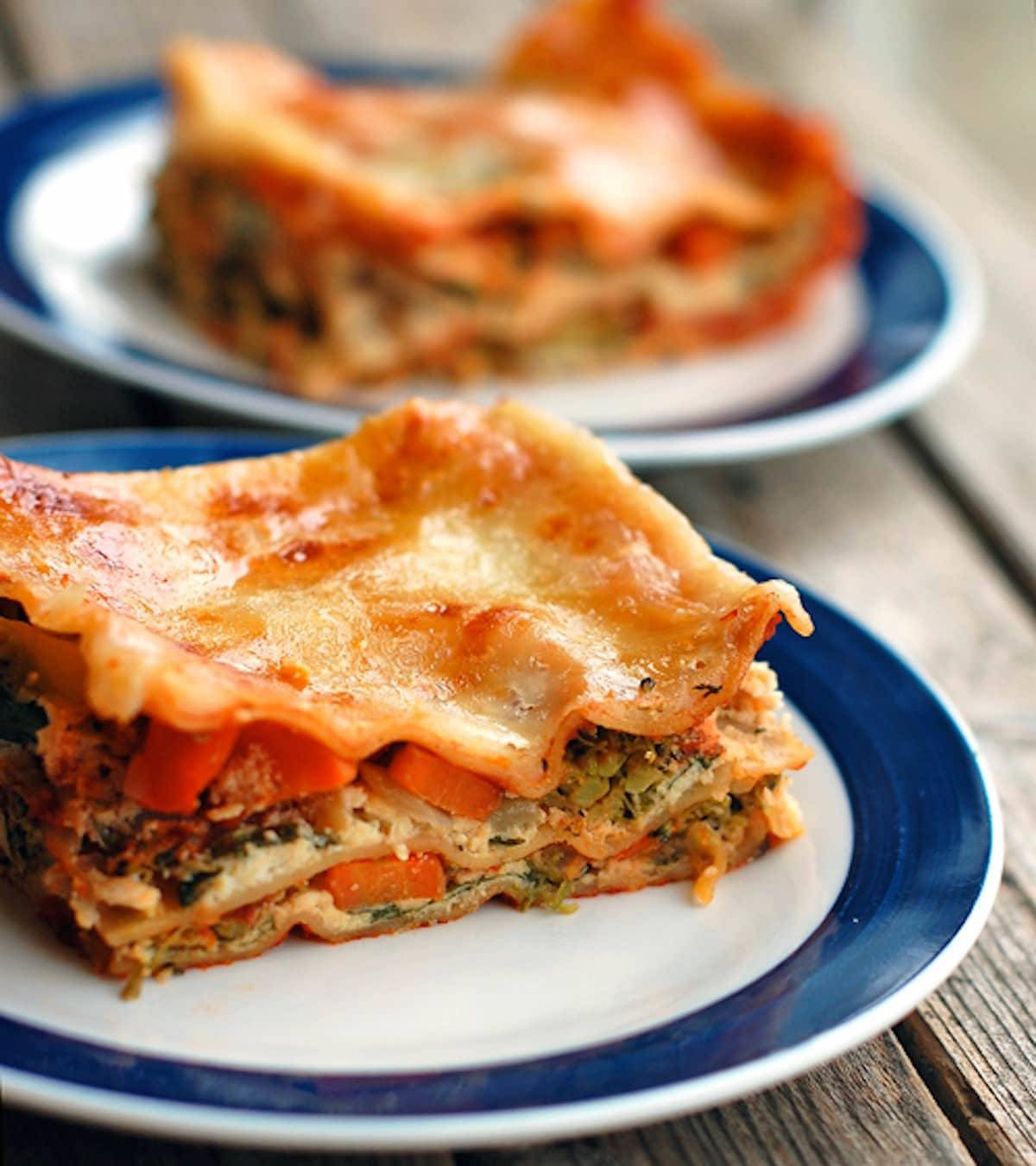 Veggie lasagna full of chopped broccoli, carrots, cauliflower, spinach, ricotta cheese, and tomato sauce on a plate.