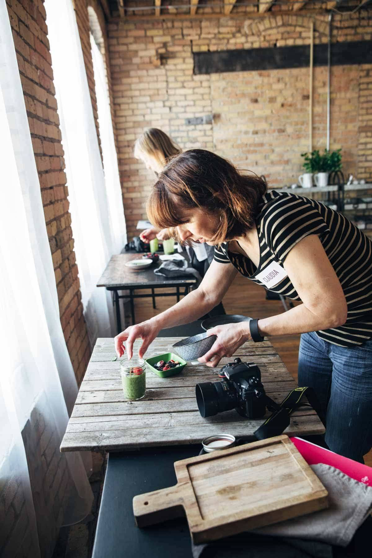 Woman styling food in a jar to photograph.